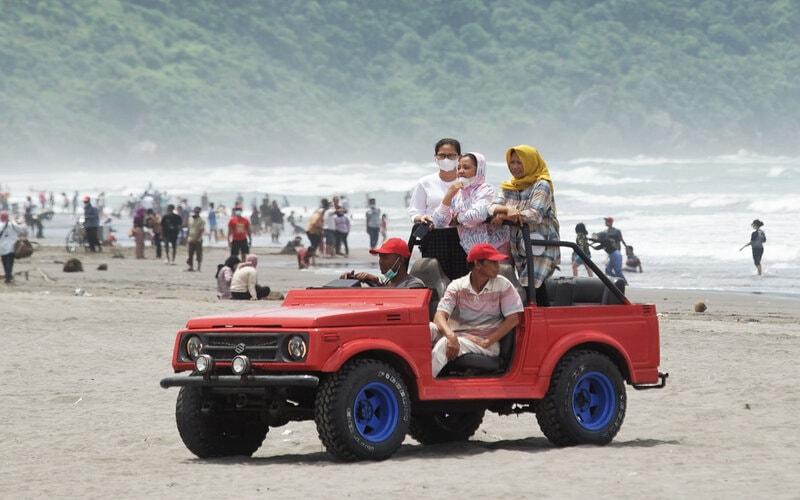 Ilustrasi wisatawan di pantai saat liburan. - Antara/Andreas Fitri Atmoko