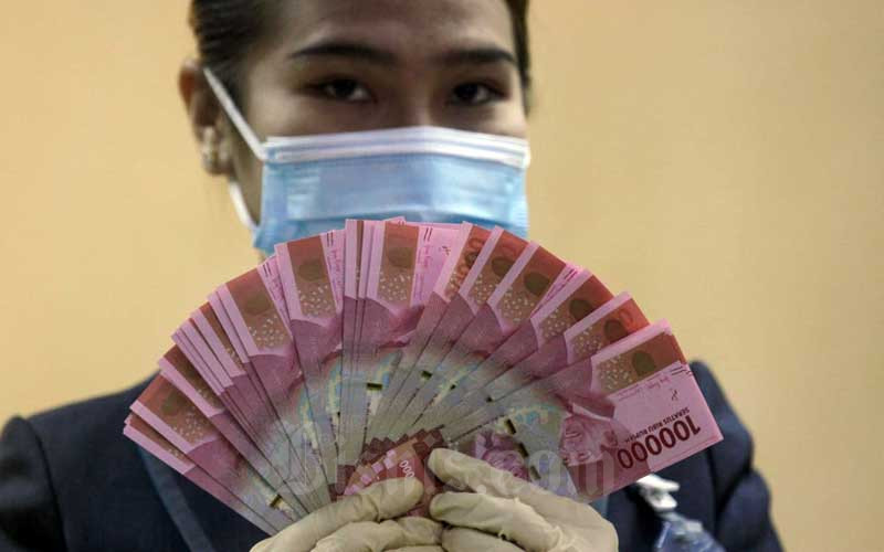 Karyawati menunjukkan mata uang rupiah dan dolar AS di salah satu kantor cabang PT Bank Negara Indonesia (Persero) Tbk. di Jakarta, Selasa (5/1/2021). Bisnis - Arief Hermawan P