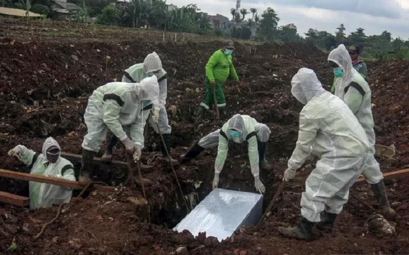 Petugas pemakaman menguburkan jenazah korban Covid-19 di TPU Srengseng Sawah Dua, Jagakarsa, Jakarta Selatan, Selasa, (2/2/2021). - Antara