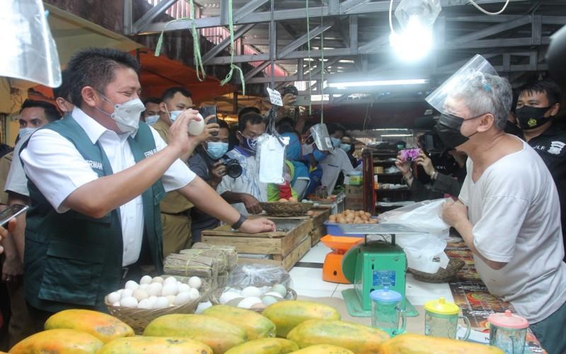 Gubernur Sumsel Herman Deru (kiri) berbincang dengan pedagang di pasar tradisional Palembang.  - Istimewa