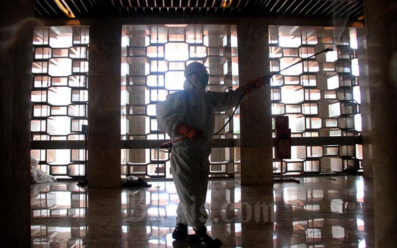 Petugas melakukan penyemprotan cairan disinfektan di area Masjid Istiqlal di Jakarta, Jumat (13/3 - 2020).