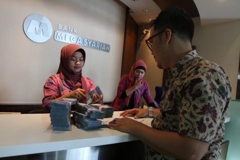 Ilustrasi / Karyawan PT Bank Mega Syariah melayani nasabah yang sedang melakukan  transaksi perbankan di salah satu kantor cabang Bank Mega Syariah.