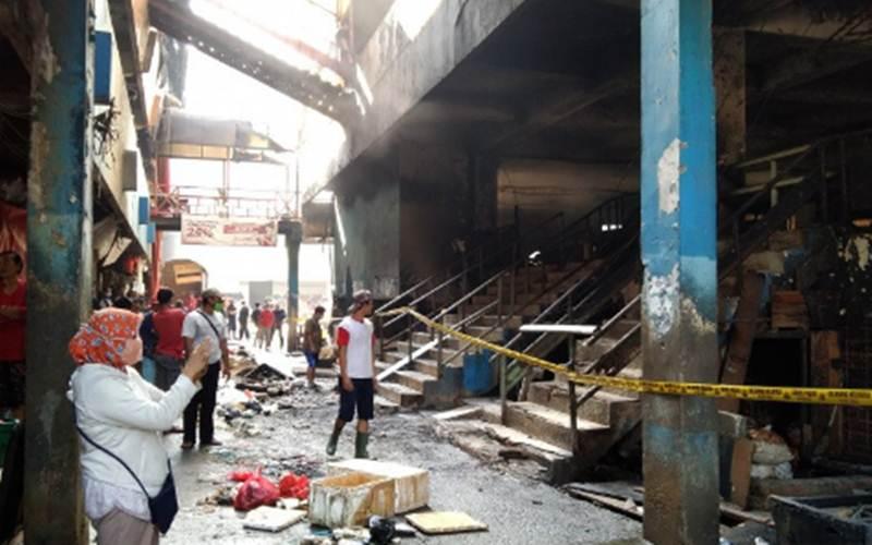 Warga mengamati puing yang hangus terbakar di Blok C Pasar Inpres Pasar Minggu, Jakarta Selatan, Selasa (13/4/2021). - Antara/Dewa Wiguna.