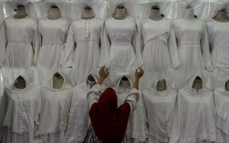 Pedagang merapikan susunan baju muslim di sebuah toko di pusat perbelanjaan, Pekanbaru, Riau, Selasa (6/4/2021). Pedagang busana muslim tersebut mengaku sepekan menjelang Ramadan penjualan perlengkapan muslim seperti baju koko, peci, sarung, mukena dan sajadah mulai mengalami peningkatan hingga 40 persen dibandingkan dengan Ramadan tahun sebelumnya. - Antara/Rony Muharrman.