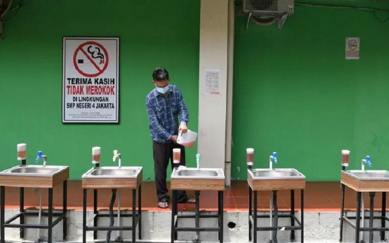 Karyawan mengisi ulang sabun cair di wastafel Sekolah Menengah Pertama (SMP) Negeri 4, Jakarta Pusat, Senin (22/3/2021). - Antara\r\n