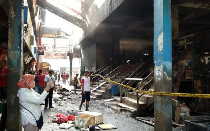 Warga mengamati puing yang hangus terbakar di Blok C Pasar Inpres Pasar Minggu, Jakarta Selatan, Selasa (13/4/2021). - Antara