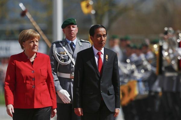 Presiden Joko Widodo (kanan) dan Kanselir Jerman Angela Merkel memeriksa pasukan, saat upacara penyambutan kedatangan Jokowi di Berlin, Jerman, Senin (18/4). - REUTERS/Hannibal Hanschke