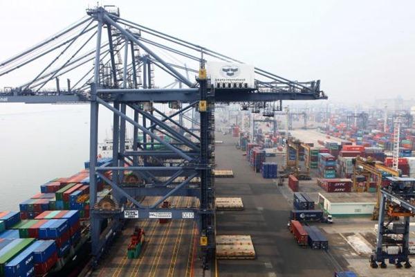 Petugas dibantu alat berat memindahan kontainer dari kapal ke atas truk pengangkut di Pelabuhan Tanjung Priok Jakarta, Selasa (17/5). JIBI/Bisnis - Dwi Prasetya