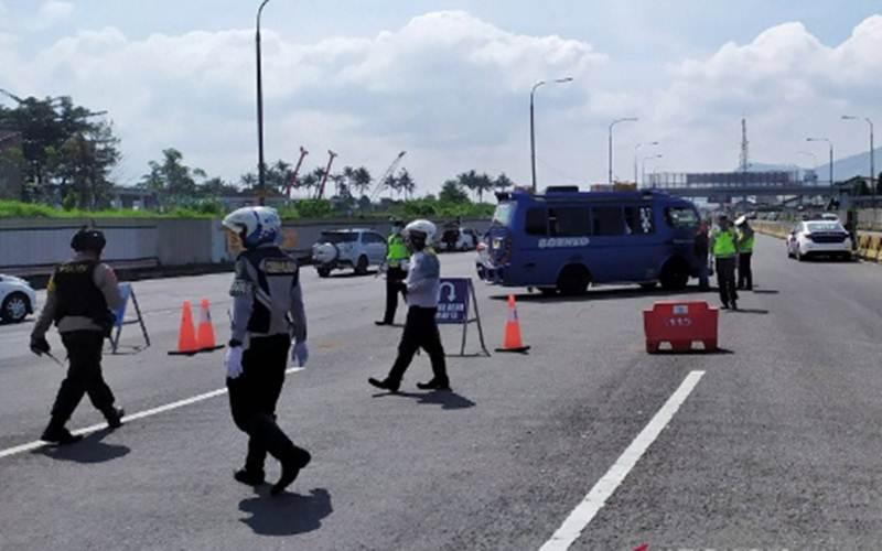 Polisi melakukan penyekatan kendaraan di Gerbang Tol Cileunyi, Kabupaten Bandung, Jawa Barat. - Antara/Bagus Ahmad Rizaldi\r\n\r\n