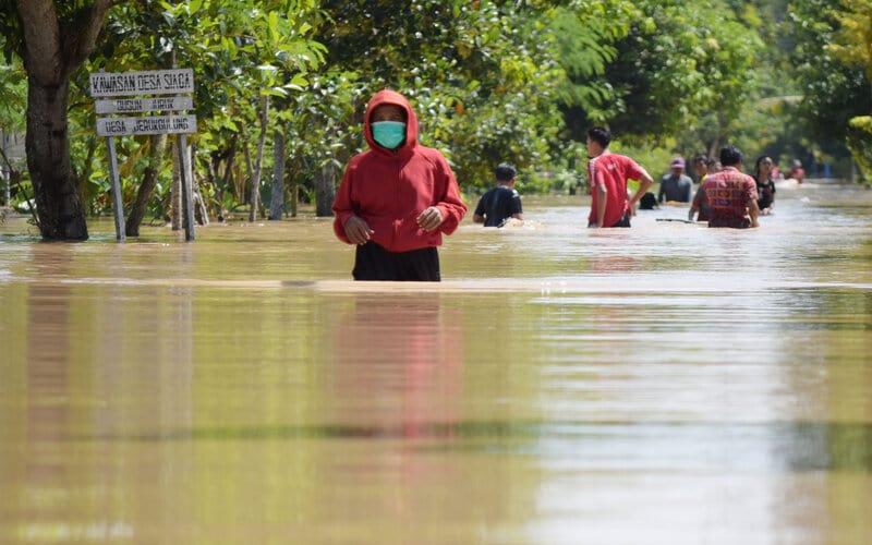 Sejumlah warga menerobos jalan yang terendam banjir di Desa Jerukgulung, Balerejo, Kabupaten Madiun, Jawa Timur, Kamis (15/4/2021). Sejumlah desa di empat kecamatan di Kabupaten Madiun terendam banjir luapan Sungai Jeroan akibat hujan deras Rabu (14/4) sore hingga malam. - Antara/Siswowidodo.