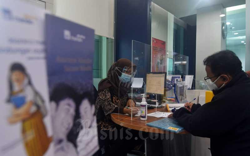 Karyawan melayani nasabah AXA Mandiri di  Jakarta, Rabu (3/1/2021). Bisnis - Abdurachman