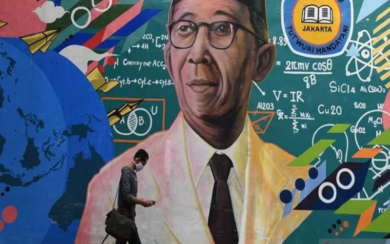 Calon peserta didik melintas di depan mural Bapak Pendidikan Nasional Ki Hajar Dewantara usai melaporkan diri dan verifikasi data pada jalur tahap akhir Penerimaan Peserta Didik Baru (PPDB) di Posko PPDB SMAN 70 Jakarta, Rabu (8/7/2020). - Antara