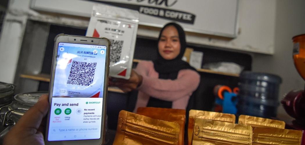 Seorang warga menggunakan pembayaran nontunai Quick Response Indonesia Standard (QRIS) saat membeli kopi di warung kopi Jalik Rumbuk di Mataram, NTB, Selasa (12/1/2021). - ANTARA FOTO/Ahmad Subaidi