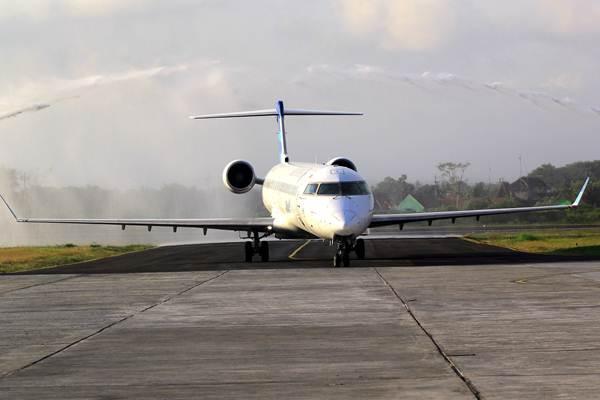 Pesawat Garuda Indonesia disambut siraman air menggunakan water cannon saat tiba di Bandara Blimbingsari, Banyuwangi, Jawa Timur, Jumat (8/9). - ANTARA/Budi Candra Setya