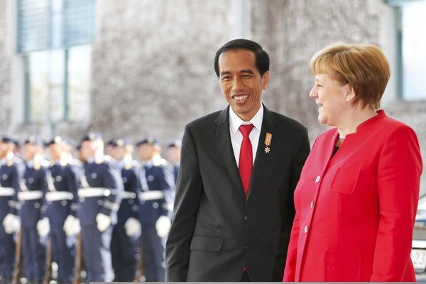 Presiden Joko Widodo (kiri) berbincang dengan Kanselir Jerman Angela Merkel saat upacara penyambutan kedatangan Jokowi di Berlin, Jerman, Senin (18/4/2016). - Reuters/Hannibal Hanschke