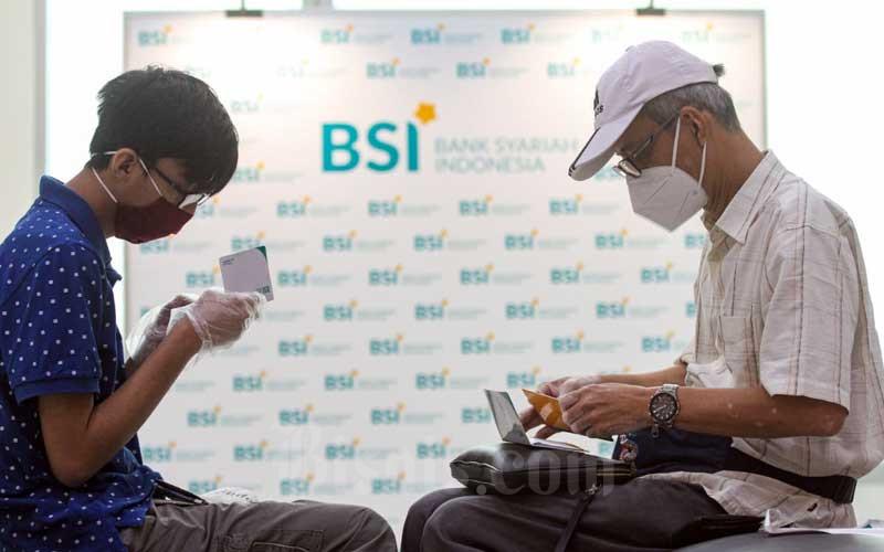 Nasabah Bank Syariah Indonesia memeriksa buku tabungan seusai membuka rekening di KC Jakarta Hasanudin, Jakarta, Selasa (2/2/2021). Bisnis - Arief Hermawan P