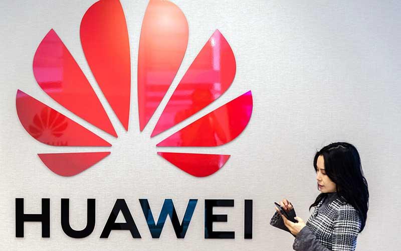 Warga menggunakan smartphone di dekat logo Huawei Technologies Co. di Brussels, Belgia.  - Bloomberg/Geert Vanden Wijngaert