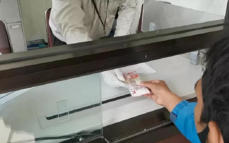 Petugas Kantor Perwakilan Bank Indonesia Provinsi NTB melayani penukaran uang pecahan khusus Rp75 ribu dengan menerapkan protokol kesehatan Covid-19. - Antara\r\n