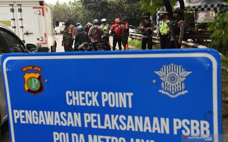 Petugas memeriksa surat izin keluar masuk (SIKM) Jakarta terhadap pengendara kendaraan bermotor yang melintas menuju Jakarta di perbatasan wilayah, Depok, Jawa Barat, Rabu (27/5/2020). - ANTARA FOTO/Indrianto Eko Suwarso