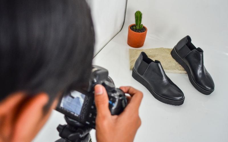 Pekerja memotret produk sepatu UMKM. - ANTARA FOTO/Adeng Bustomi