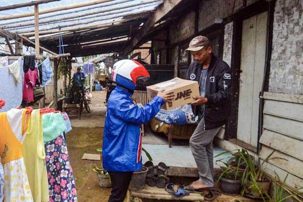 Kurir JNE memberikan paket kepada warga yang tinggal di Desa Cipanjalu, Palintang, Kabupaten Bandung, Jawa Barat, Kamis (3/1/2019). - ANTARA/Raisan Al Farisi