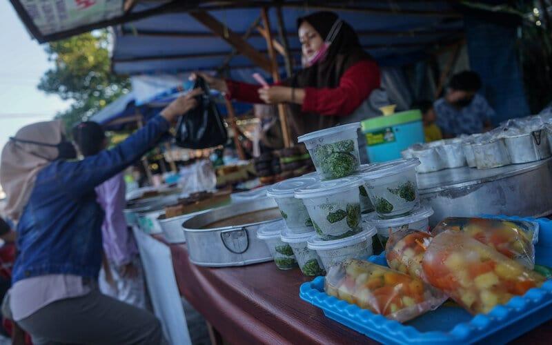 Pedagang melayani pembeli makanan untuk berbuka puasa (takjil) di kawasan Jalan Riau, Palangkaraya, Kalimantan Tengah, Kamis (15/4/2021). Menurut pedagang, penjualan takjil pada bulan Ramadan tahun ini penjualan takjil mulai meningkat dibandingkan tahun lalu karena sudah tidak adanya penerapan PSBB di Kota Palangkaraya dan daya beli masyakarat kembali membaik. - Antara/Makna Zaezar.