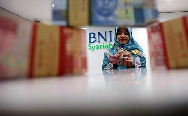 Ilustrasi - Karyawan menata uang Rupiah di kantor Bank BNI Syariah di Jakarta. Bisnis - Abdullah Azzam