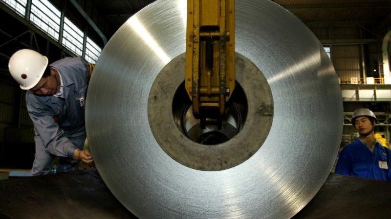 Pekerja Tiongkok membongkar gulungan pelat timah di pabrik di pinggiran Shanghai. -  File foto REUTERS / Claro Cortes