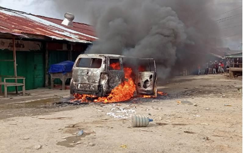 Satu unit mobil milik pelaku penganiayaan di pasar sentral Remu Kota Sorong dibakar massa, Senin (19/4) sore. - Antara/Ernes Broning Kakisina