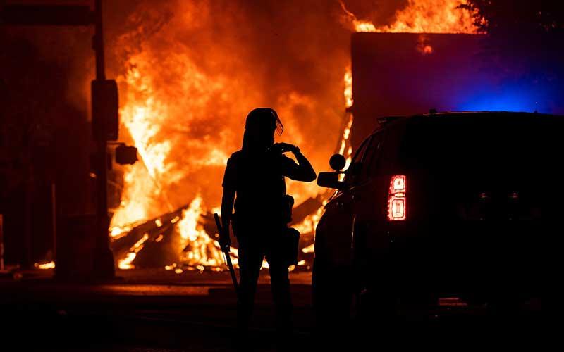 Petugas berada di dekat api saat aksi protes atas kematian George Floyd di Minneapolis, Amerika Serikat, Senin (1/6/2020). Bloomberg/Getty Images - Stephen Maturen