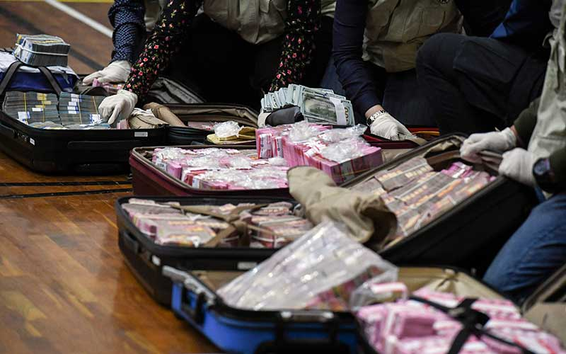 Penyidik KPK menunjukan barang bukti uang tunai saat konferensi pers terkait Operasi Tangkap Tangan (OTT) tindak pidana korupsi pada program bantuan sosial di Kementerian Sosial untuk penanganan Covid-19 senilai Ro14,5 miliar di Gedung KPK, Jakarta, Minggu (6/12/2020) dini hari. - Antara/Hafidz Mubarak A