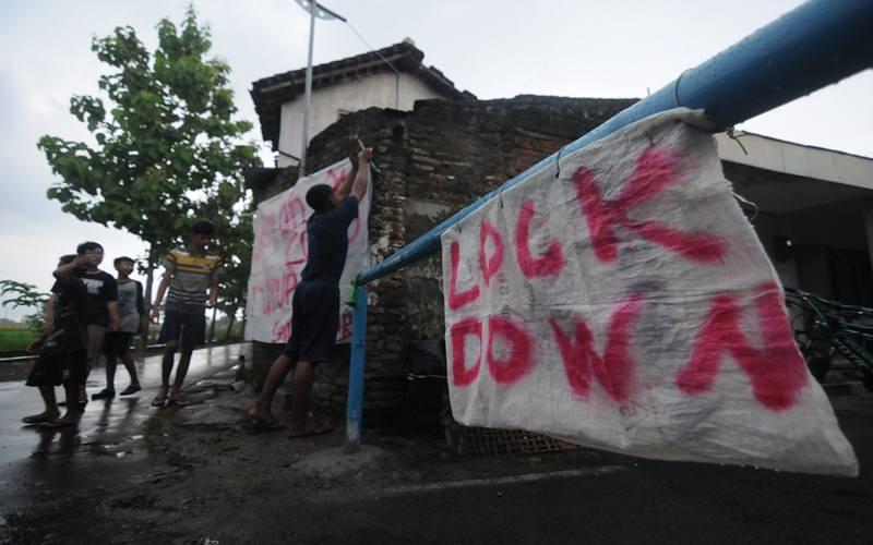 Warga memasang spanduk pada portal karantina wilayah di Bendosari, Sawit, Boyolali, Jawa Tengah, Selasa (31/3/2020).  - Antara/Aloysius Jarot Nugroho