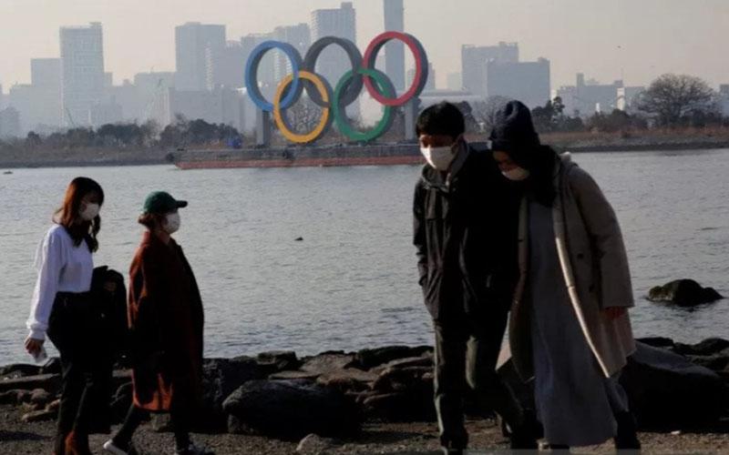 Warga memakai masker untuk mencegah penularan virus Covid-19 dengan latar belakang cincin Olimpiade raksasa di Tokyo, Jepang./Antara - Reuters
