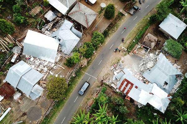 Warga melintasi rumah-rumah yang rusak akibat gempa bumi di Desa Sajang, Lombok Timur, NTB, Senin (30/7/2018). - Antara/Akbar Nugroho Gumay