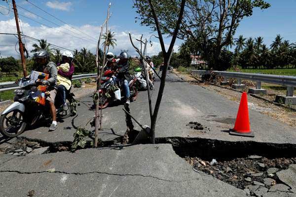 Warga mengendarai sepeda motor menghindari jalan yang rusak akibat gempa, di Lombok Utara, NTB, Selasa (7/8/2018). - Reuters/Beawiharta