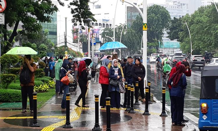 Sejumlah karyawan menunggu angkutan umum di kawasan Sudirman Jakarta Pusat Selasa (25/2/2020). Angkutan umum sulit didapat karena Jakarta kebanjiran. JIBI/Bisnis - Anya Dhyaksa