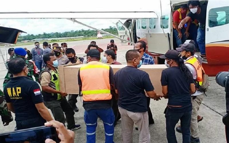 Dokumentasi - Peti jenazah dua guru korban korban penembakan oleh KKB diturunkan dari pesawat Dabi Air dan dimasukan ke dalam mobil ambulans untuk dibawa ke kamar jenazah RSUD Mimika, Sabtu (10/4/2021). - Antara