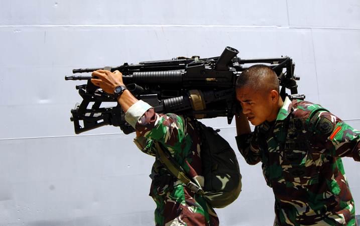 Anggota TNI Angkatan Darat mengangkat senjata usai apel pemberangkatan Satgas ke Papua di Pelabuhan Sukarno Hatta, Makassar, Sulawesi Selatan, Minggu (3/3/2019). - ANTARA/Abriawan Abhe