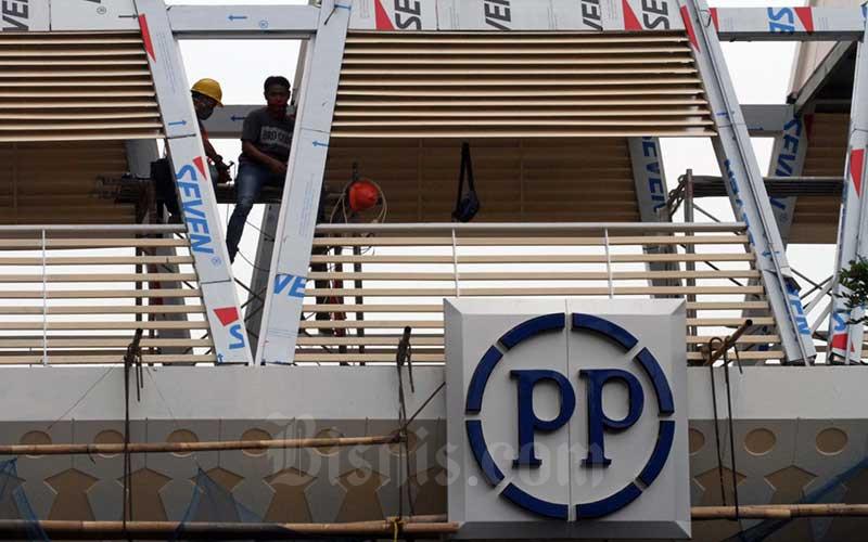 Pekerja beraktivitas di dekat logo PT PP Properti Tbk. di Depok, Jawa Barat, Sabtu (9/5/2020). Bisnis - Dedi Gunawan
