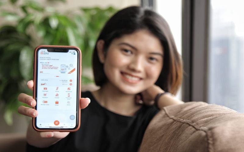 Salah satu model menunjukkan aplikasi BNI Mobile Banking di telepon genggamnya.  - Dok. BNI