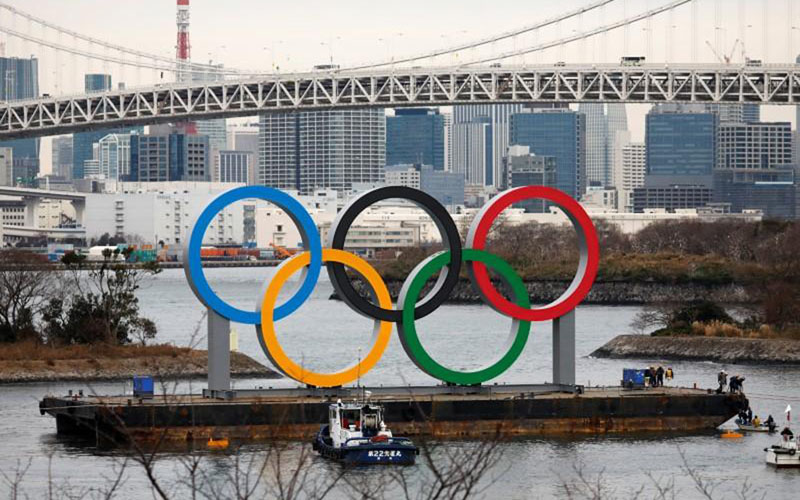 Cincin Olimpiade raksasa dipasang di area tepi laut dengan Jembatan Pelangi sebagai latar belakang, di Taman Laut Odaiba di Tokyo, Jepang, foto file 17 Januari 2020. - Reuters