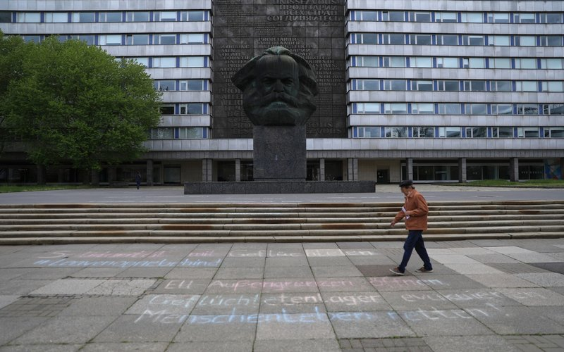 Pejalan kaki melewati patung wajah Karl Marx di Chemnitz, Jerman -  Bloomberg / Krisztian Bocsi