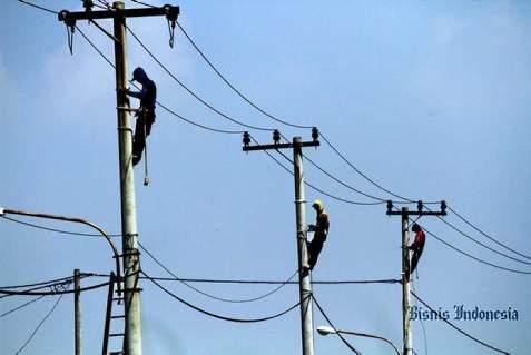 Ilustrasi: Pekerja melakukan pemeliharaan jaringan listrik. - Bisnis