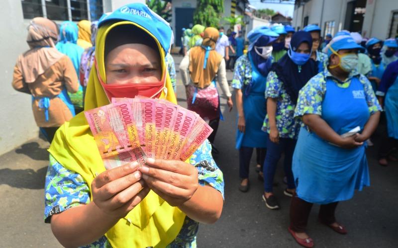 Pekerja menunjukkan uang Tunjangan Hari Raya (THR) Lebaran yang diterimanya di pabrik rokok PT Djarum, Kudus, Jawa Tengah, Selasa (12/5/2020). - ANTARA FOTO/Yusuf Nugroho