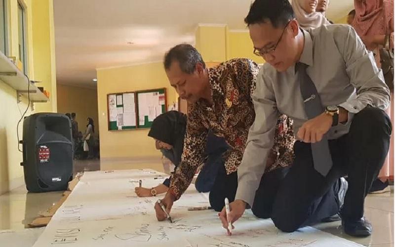 Wakil Rektor I Undip Semarang Budi Setiyono menandatangani petisi penolakan usulan revisi UU KPK di Semarang. - Antara\r\n