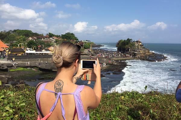Ilustrasi-Wisatawan sedang mengabadikan Daya Tarik Wisata Tanah Lot, Bali. - Bisnis/Feri Kristianto