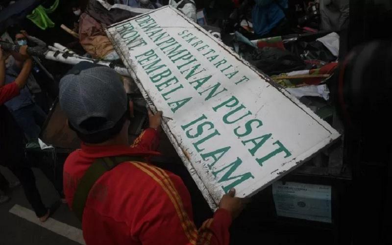 Petugas membongkar atribut saat melakukan penutupan markas DPP Front Pembela Islam (FPI) di Petamburan, Jakarta, Rabu (30/12/2020).  - Antara\r\n