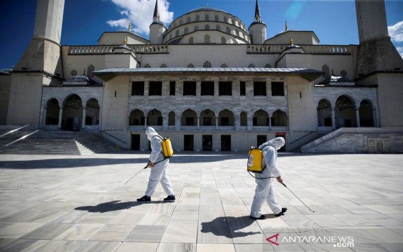 Petugas kota dengan alat pelindung diri menyemprotkan disinfektan ke halaman Masjid Kocatepe untuk mencegah penyebaran virus corona (Covid-19), selama bulan suci Ramadan di Ankara, Turki, Kamis (15/4/2021)./ANTARA FOTO/REUTERS-Cagla Gurdogan - WSJ