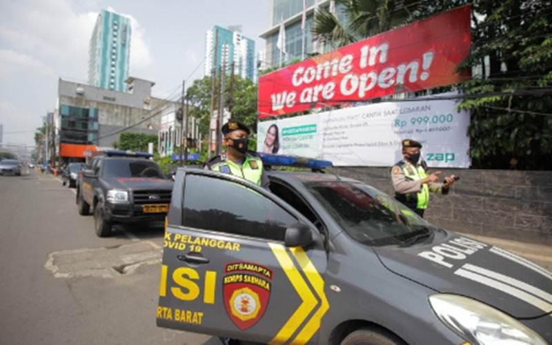 Sejumlah polisi berjaga di sekitar Hotel Holiday Inn Jalan Gajah Mada, Jakarta, Minggu (25/4/2021). Satuan Tugas Penanganan Covid-19 menyiapkan Hotel Holiday Inn sebagai tempat karantina terpusat bagi 141 warga negara asing khususnya warna negara India yang negatif Covid-19 untuk dilakukan pemantauan selama 14 hari ke depan./Antara - Reno Esnir