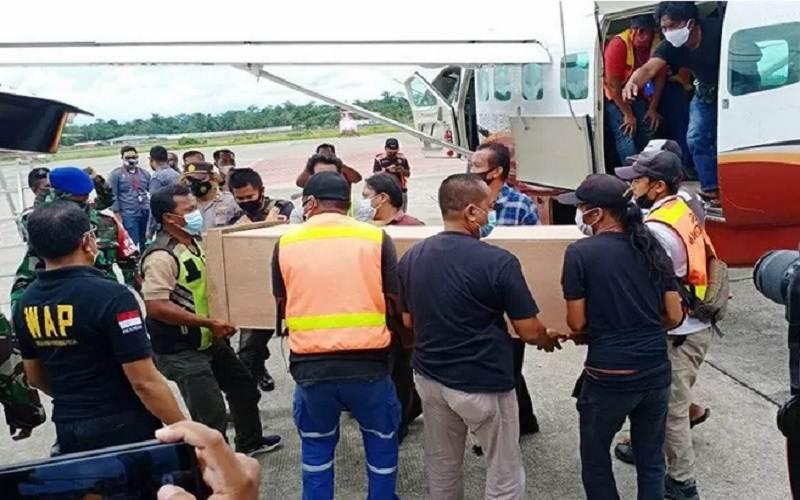 Peti jenazah dua guru korban korban penembakan oleh KKB diturunkan dari pesawat Dabi Air dan dimasukan ke dalam mobil ambulans untuk dibawa ke kamar jenazah RSUD Mimika, Sabtu (10/4/2021). - Antara